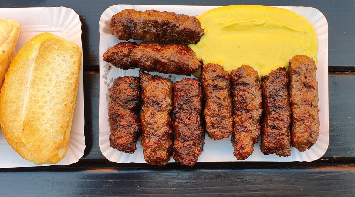 Romanian mici served on carton with mustard and bread.